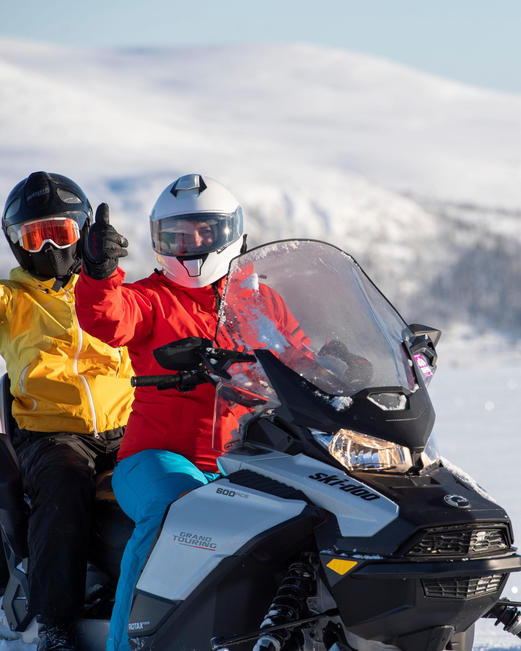 To jenter som viser tommel opp på guidet snøscootertur i Engerdal, arrangert av bookTrysilonline