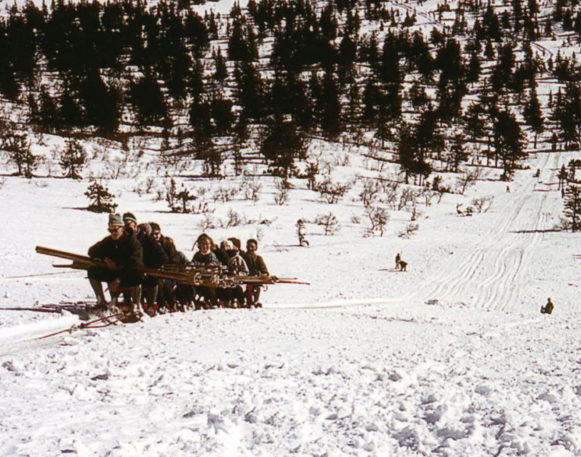 Gammelt bilde fra gamledager med folk på ski
