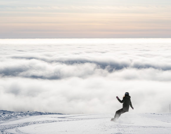 Jente på snowboard på toppen av Trysilfjellet